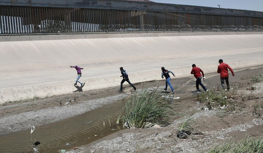 In this June 15, 2019, file photo, migrants cross the Rio Grande illegally to surrender to the American authorities on the U.S.-Mexico border between Ciudad Juarez and El Paso. El Paso has swiftly become one of the busiest corridors for illegal border crossings in the U.S. after years as one of the sleepiest. (AP Photo/Christian Torres, File)