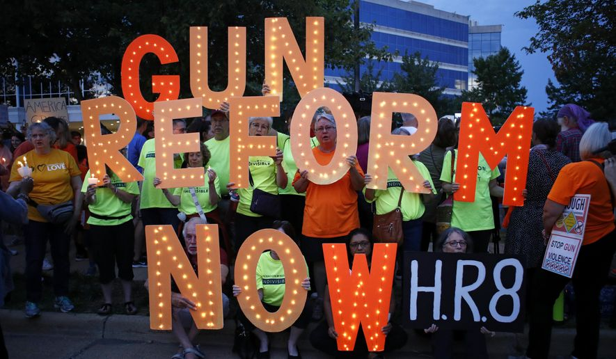 People gather at a vigil for recent victims of gun violence outside the National Rifle Association's headquarters building, Monday, Aug. 5, 2019, in Fairfax, Va. (AP Photo/Patrick Semansky)