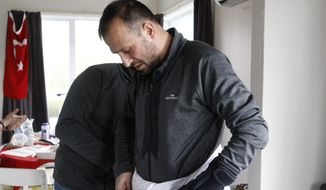 In this July 31, 2019, photo, Temel Atacocugu, who was shot nine times during the Christchurch mosque attacks, tries on the clothes he will wear during the Hajj pilgrimage, in Christchurch, New Zealand. He is among 200 survivors and relatives from the Christchurch mosque shootings who are traveling to Saudi Arabia as guests of King Salman for the Hajj pilgrimage, a trip many hope will help them to heal.(AP Photo/Nick Perry)