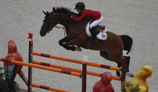 Lucy Deslauriers competes for the United States on her horse Hester in the first classification round of individual and team equestrian jumping at the Pan American Games in Lima, Peru, Tuesday, Aug. 6, 2019. Her father Mario Deslauriers, who is one of her coaches, was competing against her in the same event for Canada. (AP Photo/Rebecca Blackwell)