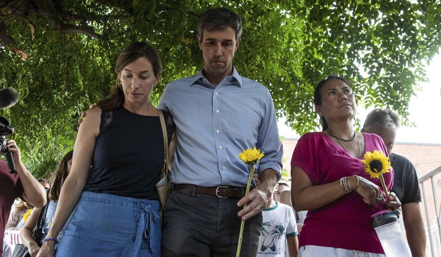 Democratic presidential candidate Beto O'Rourke walks next to his wife Amy Hoover Sanders and  Rep. Veronica Escobar Sunday, Aug. 4, 2019, during a silent march holding sunflowers in honor to the victims of a mass shooting occurred in Walmart on Saturday, Aug. 3, 2019, in El Paso, Texas. (Lola Gomez/Austin American-Statesman via AP)