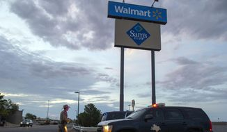 In this Aug. 4, 2019, file photo a Texas State Trooper walks back to his car while providing security outside the Walmart store in the aftermath of a mass shooting in El Paso, Texas. (AP Photo/Andres Leighton, File)