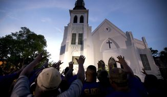 FILE - In this June 19, 2015, file photo, the men of Omega Psi Phi Fraternity Inc. lead a crowd of people in prayer outside the Emanuel AME Church after a memorial in Charleston, S.C. As the Democratic presidential field grapples with how to address a pair of shootings that killed 31, candidate Sen. Cory Booker, D-N.J., is making a gun policy speech Aug. 7, 2019, in the historic South Carolina church thats become synonymous with hate-fueled attacks on people of faith. (AP Photo/Stephen B. Morton, File)