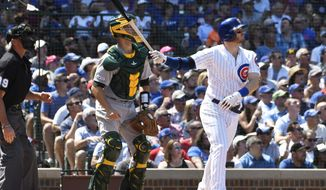 Chicago Cubs' Ian Happ (8) watches his grand slam home run against the Oakland Athletics during the fourth inning of a baseball game, Wednesday, Aug. 7, 2019, in Chicago. (AP Photo/David Banks)