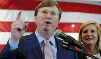 Republican Lt. Gov. Tate Reeves, a gubernatorial candidate, flanked by wife, Elee Reeves, congratulates his supporters during an appearance at his election watch party in Flowood, Miss., Tuesday, Aug. 6, 2019. Reeves was in the lead of his party primary. (AP Photo/Rogelio V. Solis)