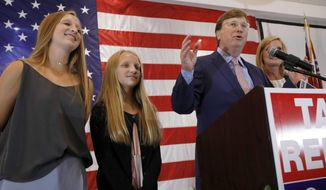 Republican Lt. Gov. Tate Reeves, a gubernatorial candidate, at podium, flanked by daughters Tyler Reeves, 14, left, and Emma Reeves, 12, congratulates his supporters during an appearance at his election watch party in Flowood, Miss., Tuesday, Aug. 6, 2019. Reeves was in the lead of his party primary. (AP Photo/Rogelio V. Solis)