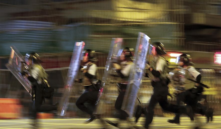 Policemen in riot gears move to disperse the residents and protesters at Sham Shui Po district in Hong Kong, Wednesday, Aug. 7, 2019. Protesters surrounded a Hong Kong police station to demand the release of a university student arrested for apparently buying laser pointers, sparking the latest confrontation in the Chinese city. (AP Photo/Vincent Thian)