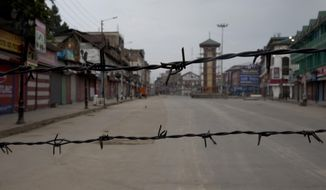 In this Tuesday, Aug. 6, 2019 photo, a deserted street is seen through a barbwire set up as blockade during curfew in Srinagar, Indian controlled Kashmir, Wednesday, Aug. 7, 2019. Authorities in Hindu-majority India clamped a complete shutdown on Kashmir as they scrapped the Muslim-majority state's special status, including exclusive hereditary rights and a separate constitution, and divided it into two territories. (AP Photo/Dar Yasin)