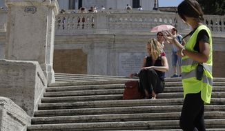 A Police officer asks a woman not to sit on the Spanish Steps, in Rome, Wednesday, Aug. 7, 2019. Police started the enforcement of a law designed to protect monuments and landmarks and are forbidding people from sitting on the Spanish steps since they are considered a monument. (AP Photo/Gregorio Borgia)