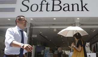 People walk by a SoftBank shop in Tokyo, Wednesday, Aug. 7, 2019. Japanese technology company SoftBank Group Corp. has seen its fiscal first quarter profit nearly quadruple to 1.122 trillion yen ($10.6 billion) as its fund investments boosted income. (AP Photo/Koji Sasahara)