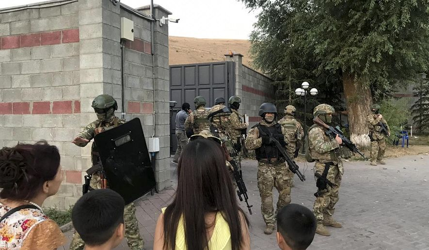 Kyrgyz special forces stand in guard at former president of Kyrgyzstan Almazbek Atambayev's residence in the village of Koi-Tash, about 20 kilometers (12 miles) south of the capital, Bishkek, Kyrgyzstan, Wednesday, Aug. 7, 2019. Gunfire is being heard outside the residence of the former president of Kyrgyzstan as police move in to try to arrest him. The Kyrgyz news site 24.kg said several people, including journalists, have been wounded in the Wednesday shooting in the village of Koi-Tash, 20 kilometers (12 miles) south of the capital, Bishkek. (AKIpress via AP)