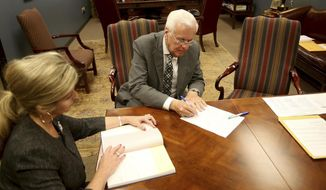Insurance commissioner Jim Donelan signs paperwork the Louisiana Secretary of State's office as he signs up to run in the upcoming election, in Baton Rouge, La., Tuesday, August 6, 2019. The candidate sign-up period for Louisiana's statewide elections ends Thursday, with the governor's race at the top of the ballot. (AP Photo/Michael DeMocker)