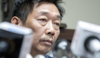 Yingying Zhang's father Ronggao Zhang, listens to a question during a press conference at lawyer Steve Beckett's law office on Wednesday, August 7 2019 Urbana, Ill. The father of the slain scholar who begged his daughter's killer to reveal what he did with her remains so that they could be returned to China for burial says his family now understands that recovering them may be impossible.  (Robin Scholz/The News-Gazette via AP )