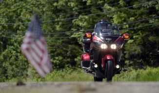 """FILE - In a Saturday, June 22, 2019 file photo, a motorcycle passes the scene of a fatal accident on Route 2 in Randolph, N.H. Massachusetts legislators probing the state's Registry of Motor Vehicles in the aftermath of a crash that killed seven motorcyclists are growing impatient with state officials' response to document requests and """"losing confidence"""" in the willingness of Gov. Charlie Baker's administration to cooperate with the investigation, according to a new letter  delivered Tuesday to state Secretary of Transportation Stephanie Pollack. (Paul Hayes/Caledonian-Record via AP, File)"""