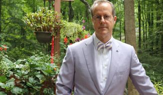 In a Thursday, Aug. 1, 2019 photo, Bruce Fleming, a tenured civilian English professor who has been a longtime critic of the Naval Academy, stands on the deck of his home after an interview in Davidsonville, Maryland. Fleming, who was fired by the academy last year, was reinstated last month to his job with back pay by an administrative law judge. The academy informed Fleming on Wednesday, Aug. 7 that it is appealing the decision. (AP Photo/Brian Witte)