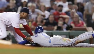 Boston Red Sox third baseman Rafael Devers, left, tags out Kansas City Royals' Billy Hamilton, right, who tried to advance to third on a flyout during the fourth inning of a baseball game at Fenway Park in Boston, Wednesday, Aug. 7, 2019. (AP Photo/Charles Krupa)