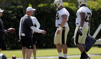 FILE - In this May 23, 2019, file photo, New Orleans Saints rookie center Erik McCoy (78) talks with offensive line coach Dan Roushar during NFL football practice in Metairie, La. Saints coach Sean Payton stopped short of declaring top draft choice McCoy the starting center in the preseason opener. Yet, if recent practices are any indication, the 6-foot-4, 315-pound rookie out of Texas A&M has as good a chance as anyone to open the season snapping the ball to 40-year-old, record-setting quarterback Drew Brees. (AP Photo/Gerald Herbert, File)