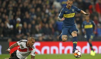 FILE - In this Sunday, Dec. 9, 2018 file photo Dario Benedetto of Argentina's Boca Juniors, right, runs with the ball to score against Argentina's River Plate, as Javier Pinola of River falls down during the Copa Libertadores final soccer match at the Santiago Bernabeu stadium in Madrid, Spain. (AP Photo/Thanassis Stavrakis, File)