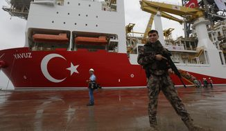 FILE - In this Thursday, June 20, 2019 file photo, a Turkish police officer patrols the dock, backdropped by the drilling ship 'Yavuz' to be dispatched to the Mediterranean, at the port of Dilovasi, outside Istanbul. Turkey's state-run news Anadolu Agency quoted Wednesday, Aug. 7, 2019, Turkey's Energy Minister Fatih Donmez as saying that Yavuz, had begun operations in an area off the Karpas peninsula on Cyprus' east coast. Cyprus says Turkey's drilling activities are unlawful while the European Union announced sanctions against Turkey. (AP Photo/Lefteris Pitarakis, File)