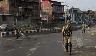 Indian Paramilitary soldiers drag barbwire as they prepare to impose curfew in Srinagar, Indian controlled Kashmir, Wednesday, Aug. 7, 2019. Authorities in Hindu-majority India clamped a complete shutdown on Kashmir as they scrapped the Muslim-majority state's special status, including exclusive hereditary rights and a separate constitution, and divided it into two territories. (AP Photo/Dar Yasin)