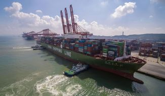 In this Aug. 6, 2019, photo, tugboats manuever a container ship at a port in Qingdao in eastern China's Shandong province. Chinese imports of American goods plunged in July as a tariff war with Washington intensified. (Chinatopix via AP)