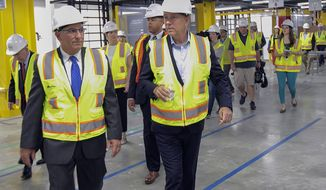 FILE - In this June 20, 2019 file photo, state Sen. Len Fasano, left, and Connecticut Gov. Ned Lamont tour Amazon's newest Robotics Fulfillment Center in North Haven, Conn. Records show Lamont has made it a priority in his first months in office to reach out to top executives across Connecticut, embarking on a kind of charm offensive in a state that has seen its reputation take a hit from the departure of some of its best-known employers. (Dave Zajac/Record-Journal via AP, File)