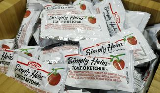 Packets of Simply Heinz ketchup fill a cafeteria condiment box, Thursday, Aug. 8, 2019. Kraft Heinz Co. on Thursday reported second-quarter net income of $449 million. (AP Photo/Richard Drew)