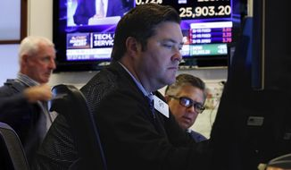 FILE - In this Aug. 6, 2019, file photo trader Terrance McCauley, center, works on the floor of the New York Stock Exchange. The U.S. stock market opens at 9:30 a.m. EDT on Thursday, Aug. 8. (AP Photo/Richard Drew, File)