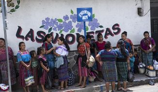 Women wait at a bus stop in the central park, of San Martin Jilotepeque, Guatemala, Sunday, August 4, 2019. San Martin Jilotepeque, like other towns in Guatemala, depends to a large extent on remittances, the money sent home by migrants living in the United States. (AP Photo/ Oliver de Ros)
