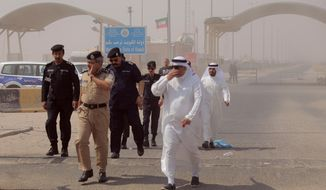 Kuwaiti officials arrive for a handover ceremony for the remains of 48 Kuwaiti citizens in Safwan border crossing, Iraq, Thursday, Aug. 8, 2019. Iraqi and Kuwaiti state media say Iraq has handed over to Kuwait the remains of 48 Kuwaitis who went missing during the 1991 Gulf War. (AP Photo)