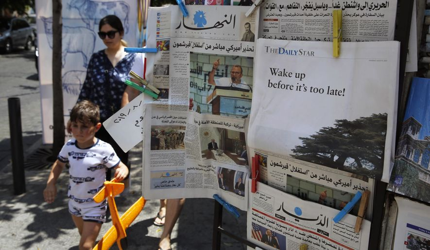 "People walk past a shop selling newspapers in Beirut, Lebanon, Thursday, Aug. 8, 2019. Lebanon's only English-language daily The Daily Star is protesting the country's deteriorating economic and political conditions by publishing a blank edition. The back page had a photo of the cedar tree, a national symbol, with a caption reading: ""Wake up before it's too late!"" (AP Photo/Bilal Hussein)"