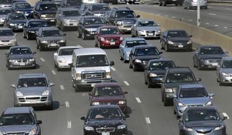 FILE - In this July 12, 2012 file photo, commuters head out of town on the Massachusetts Turnpike in Boston. Gov. Charlie Baker will release a report on Thursday, Aug. 8, 2019, from the state Department of Transportation on the state's traffic congestion. (AP Photo/Charles Krupa, File)