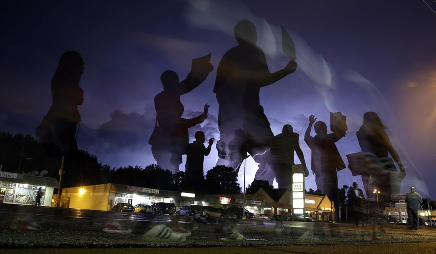 In this Aug. 20, 2014, file photo, protesters march in the street as lightning flashes in the distance in Ferguson, Mo. Michael Brown's death on Aug. 9, 2014, at the hands of a white Missouri police officer stands as a seismic moment of race relations in America. The fledgling Black Lives Matter movement found its voice, police departments fell under intense scrutiny, progressive prosecutors were elected and court policies revised. (AP Photo/Jeff Roberson, File)