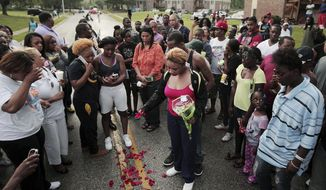 FILE - In this Aug. 9, 2014, file photo, Lezley McSpadden, center, drops rose petals on the bloodstains from her son Michael Brown, who was shot and killed by a police officer in the middle of the street in Ferguson, Mo. (Huy Mach/St. Louis Post-Dispatch via AP, File)