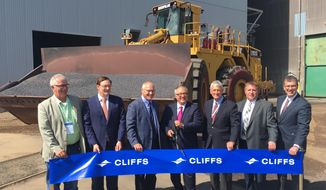 Cleveland Cliffs CEO Lourenco Goncalves, flanked by current 8th District Congressman Pete Stauber and former Congressman Rick Nolan, cuts the ceremonial ribbon on Tuesday, Aug. 6, 2019, for Northshore Mining's $100 million upgrade to produce a new kind of iron pellet to feed a growing segment of the steel industry. (Dan Kraker/Minnesota Public Radio via AP)