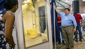 "Illinois Gov. JB Pritzker, center, and Illinois Lt. Gov. Juliana Stratton, left, unveil the 2019 Illinois State Fair Butter Cow during a ceremony inside the Dairy Building on the Illinois State Fairgrounds, Wednesday, Aug. 7, 2019, in Springfield, Ill. The theme of this year's butter cow, made of 800 pounds of recycled butter by artist Sarah Pratt, is ""Building Our Future"" and contains nine hearts hidden within the sculpture that represent the essential nutrients found in dairy products. (Justin L. Fowler/The State Journal-Register via AP)"