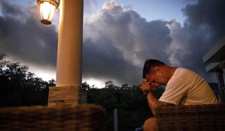 "Walter Denton prays as the sun rises in his backyard in Agat, Guam, Saturday, May 11, 2019. Denton is one of over 200 former altar boys, students and Boy Scouts who are now suing Guam's Catholic archdiocese over decades of sexual abuse they say they suffered at the hands of almost three dozen clergy, teachers and scoutmasters. ""He took everything from me. From that day forward my demeanor changed. I break down, I hurt everyday and I still hurt,"" said Denton. But, he adds, ""he didn't ruin my faith. I still believe in God."" Former Archbishop of Agana, Anthony Apuron denies the allegations. (AP Photo/David Goldman)"