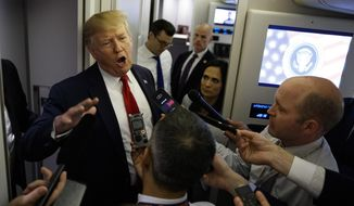 President Donald Trump talks to reporters aboard Air Force One after visiting Dayton, Ohio and El Paso, Texas, Wednesday, Aug. 7, 2019. (AP Photo/Evan Vucci)