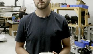 FILE - In this Aug. 1, 2018, file photo, Cody Wilson, with Defense Distributed, holds a 3D-printed gun called the Liberator at his shop, in Austin, Texas. On Friday, Aug. 9, 2019, Wilson, who sparked a nationwide legal fight over the constitutionality of firearms made with a 3D printer, pleaded guilty to having sex with an underage girl. (AP Photo/Eric Gay, File)