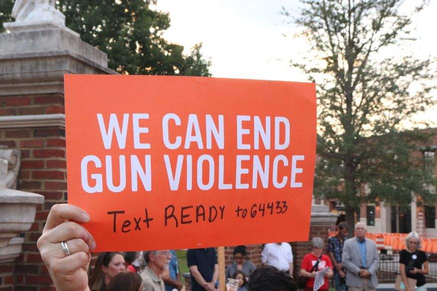 Protesters hold a rally against gun Violence on Aug. 5, 2019 at Toomer's Corner Auburn, Ala.   Mothers, fathers, friends and supporters gathered together at Toomer's Corner in downtown Auburn to honor those who have died from gun violence at the Moms Demand Action event. (Hannah Lester/Opelika-Auburn News via AP)
