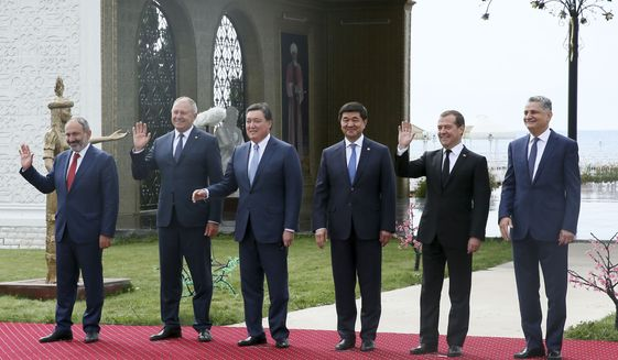Eurasian economic delegates, from left, Armenian Prime Minister Nikol Pashinyan, Belarusian Prime Minister Siarhiej Rumas, Kazakhstan Prime Minister Askar Mamin, Kyrgyz Prime Minister Mukhammedkalyi Abylgaziev, Russian Prime Minister Dmitry Medvedev and Tigran Sargsyan, chairman of the Board of the Eurasian Economic Commission, as they pose for a photo prior to the Eurasian Economic Union Intergovernmental Council in Cholpon-Ata, Kyrgyzstan, Friday, Aug. 9, 2019. (Yekaterina Shtukina, Sputnik, Government Pool Photo via AP)
