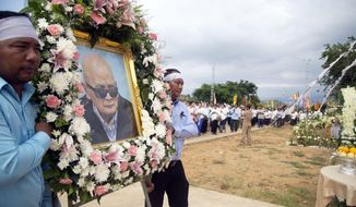Relatives carry a portrait of former Khmer Rouge's chief ideologist and No. 2 leader, Nuon Chea, during his funeral procession in Pailin in northwestern Phnom Penh, Cambodia, Friday, Aug. 9, 2019. Nuon Chea, known as Brother No. 2 and the right-hand man of Pol Pot, the leader of the brutal Communist regime that ruled Cambodia from 1975 to 1979, died Sunday at age 93. (AP Photo/Chorn Chanren)