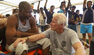 Actor Richard Gere, right, talks with migrants aboard the Open Arms Spanish humanitarian boat as it cruises in the Mediterranean Sea, Friday, Aug. 9, 2019. Open Arms has been carrying 121 migrants for a week in the central Mediterranean awaiting a safe port to dock, after it was denied entry by Italy and Malta. (AP Photo/Valerio Nicolosi)