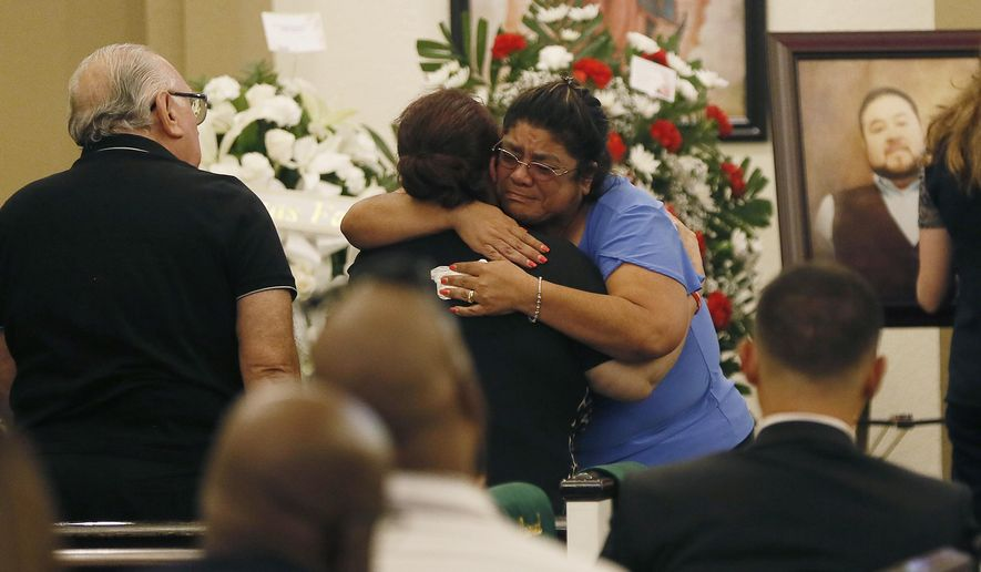 """In this Thursday, Aug. 8, 2019, photo, friends and family attend the rosary for Leonardo Campos at Sunset Funeral Home in El Paso, Texas. A memorial service was held for 41-year-old Leonardo """"Leo"""" Campos, who was killed along with his wife when a gunman opened fire at an El Paso Walmart. Leo Campos grew up in the Rio Grande Valley in South Texas but had in recent years moved to El Paso. (Briana Sanchez/The El Paso Times via AP)"""