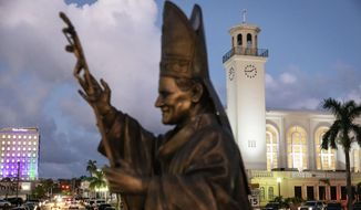 A statue of Pope John Paul II stands outside the island's main cathedral, Dulce Nombre de Maria Cathedral-Basilica, during a Mass in Hagatna, Guam, Tuesday, May 7, 2019. Those old enough to remember often cite the pontiff's visit to the island in 1981 as the most thrilling event of their lifetimes, memorialized by the bronze statue of the now-sainted pope designed to slowly rotate on a concrete pedestal. (AP Photo/David Goldman)