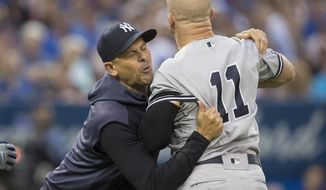 New York Yankees manager Aaron Boone holds Brett Gardner back from getting at home plate umpire Chris Segal after a called third strike during the fourth inning of the team's baseball game against the Toronto Blue Jays on Friday, Aug. 9, 2019, in Toronto. (Fred Thornhill/The Canadian Press via AP)