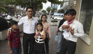 Journalists Uon Chhin, right, and Yeang Sothearin with his children walk to enter the municipal court in Phnom Penh, Cambodia, Friday, Aug. 9, 2019. The two Cambodian journalists who had worked for U.S. government-funded Radio Free Asia were back on trial Friday on espionage charges that rights groups have characterized as a flagrant attack on press freedom. Uon Chhin and Yeang Sothearin are charged with undermining national security by supplying information to a foreign state, which is punishable by up to 15 years in prison. (AP Photo/Heng Sinith)
