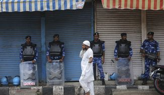 A man walks past Rapid Action Force (RAF) soldiers standing guard in Jammu, India, Friday, Aug. 9, 2019. The restrictions on public movement throughout Kashmir have forced people to stay indoors and closed shops and even clinics. All communications and the internet have been cut off. Prime Minister Modi said late Thursday the situation in the region would return to normal gradually. (AP Photo/Channi Anand)