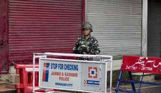 An Indian Paramilitary soldier mans a barricade on a deserted street during curfew in Srinagar, Indian controlled Kashmir, Thursday, Aug. 8, 2019. The lives of millions in India's only Muslim-majority region have been upended since the latest, and most serious, crackdown followed a decision by New Delhi to revoke the special status of Jammu and Kashmir and downgrade the Himalayan region from statehood to a territory. Kashmir is claimed in full by both India and Pakistan, and rebels have been fighting Indian rule in the portion it administers for decades. (AP Photo/Dar Yasin)