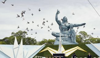 Doves fly over the Statue of Peace during a ceremony at Nagasaki Peace Park in Nagasaki, southern Japan Friday, Aug. 9, 2019 to mark the 74th anniversary of the world's second atomic bomb attack.(Kyodo News via AP)